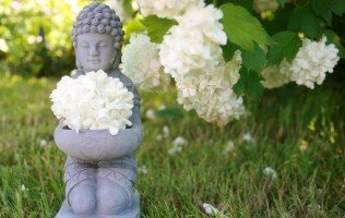 stone-buddhas-sculpture-with-flowers-in-grass